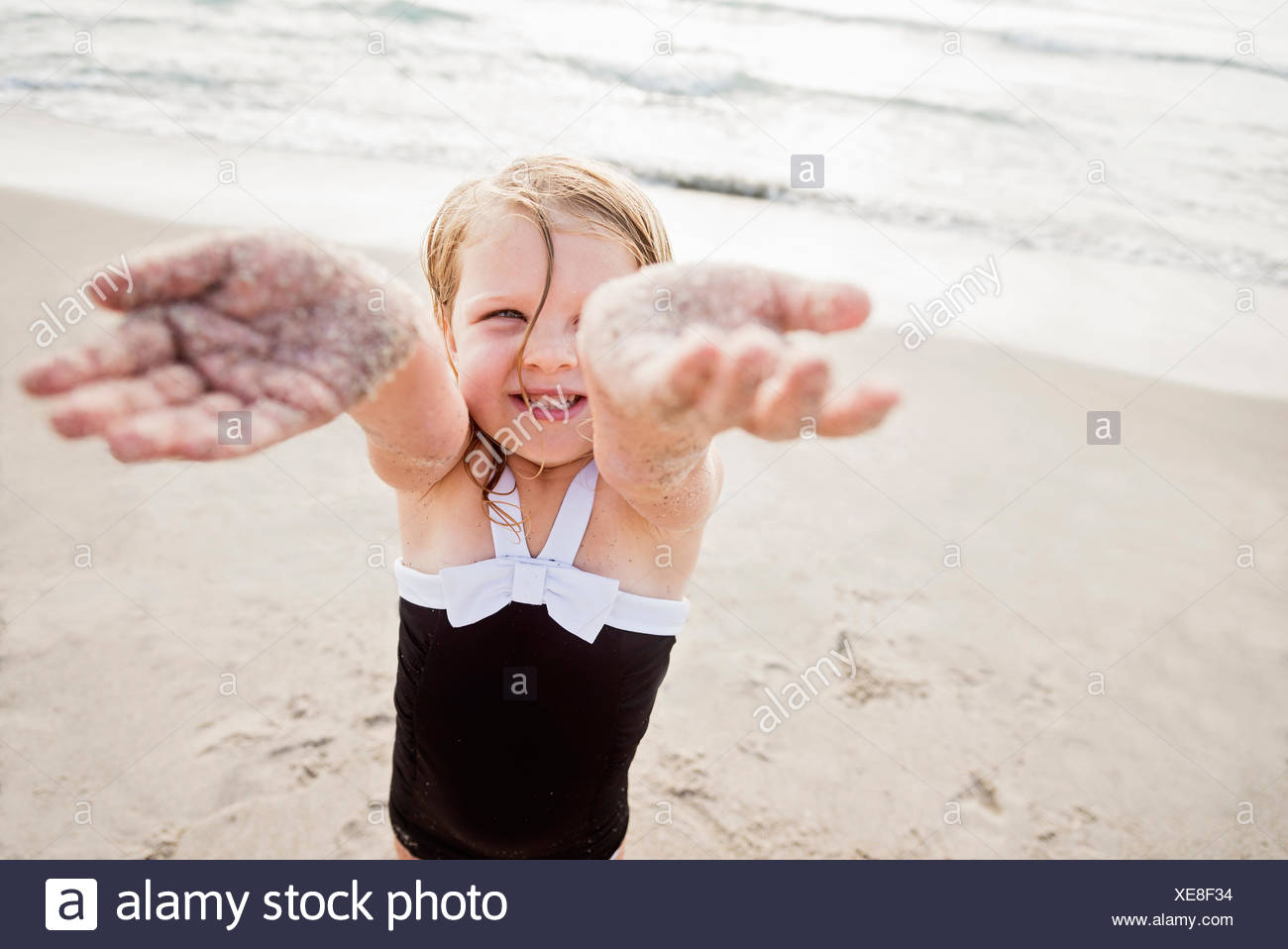 Girl (4-5) standing on beach showing her dirty hands - Stock Image