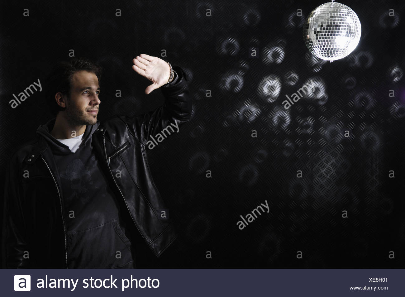 Disco, inside, disco sphere, man, young, gesture, glare, people, unshaven, 3-days beard, dark-haired, party, hand, protection, blanket, faded out, light, fiercely, shine, tin wall, light reflexions, - Stock Image