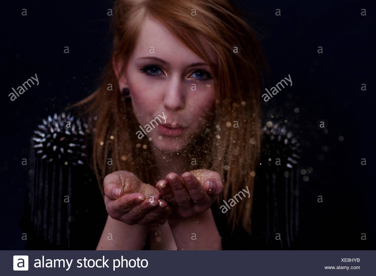 stylish dressed woman puffs glitter in the camera - Stock Image