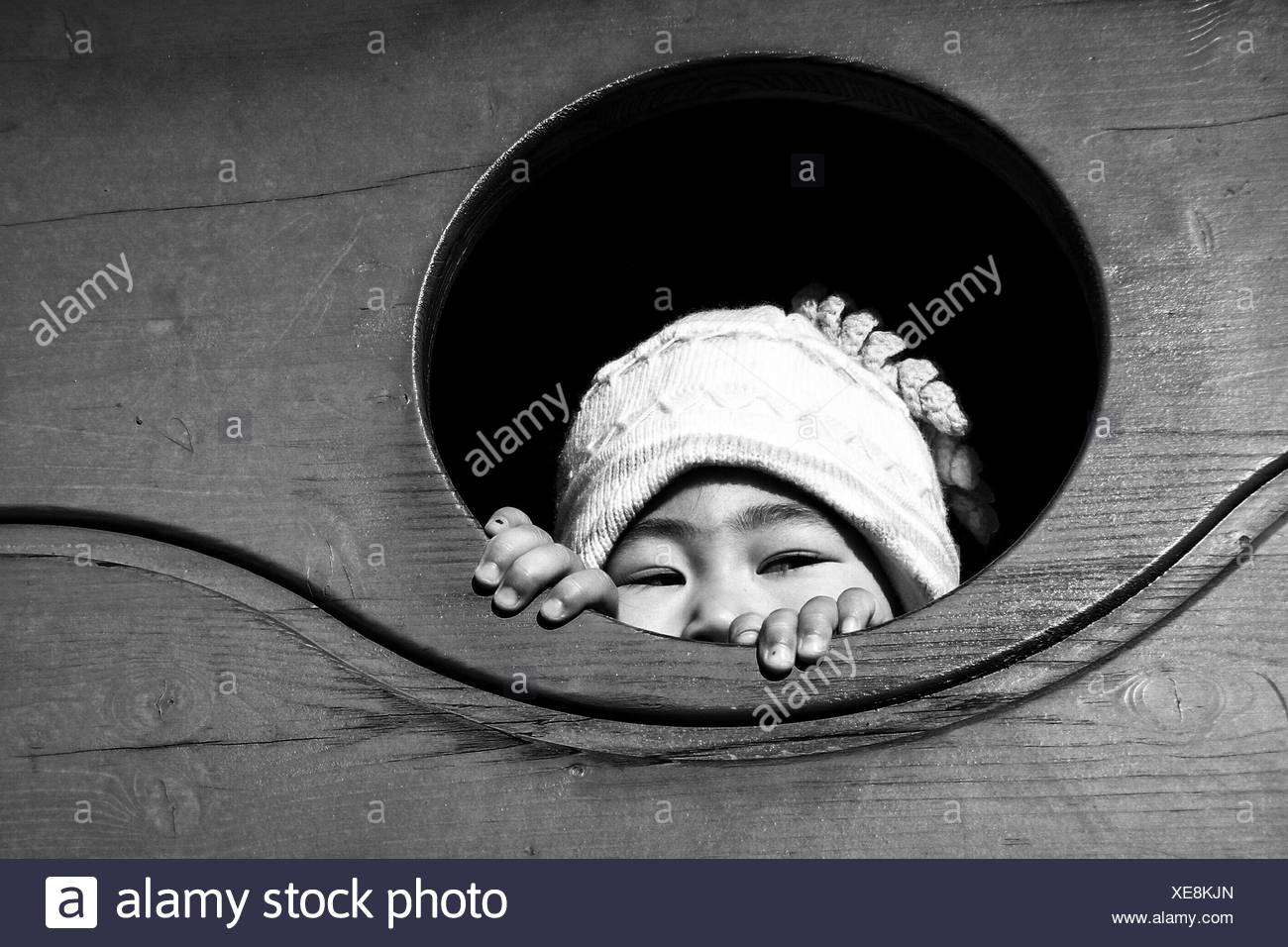 Close-Up Of Child Looking Through Window - Stock Image