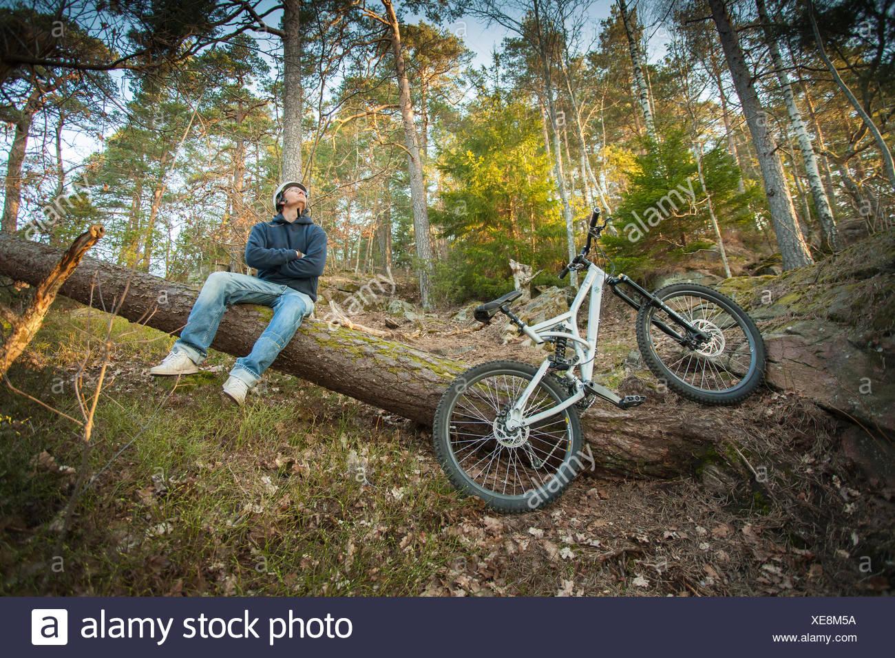 Sweden, Vastergotland, Lerum, Mountain biker sitting on tree trunk Stock Photo