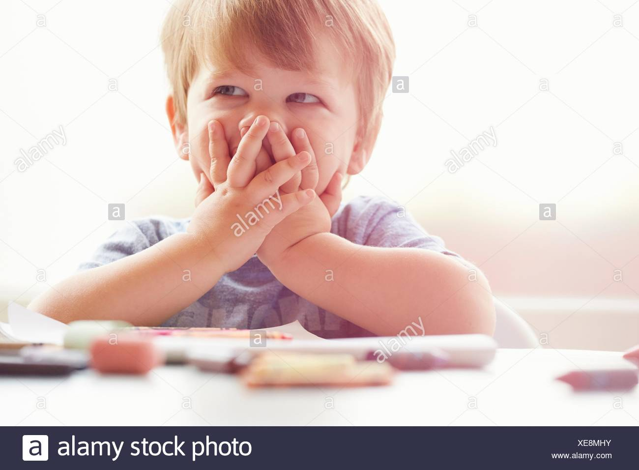 Boy sitting at table resting on elbows, covering mouth with hands, looking away Stock Photo