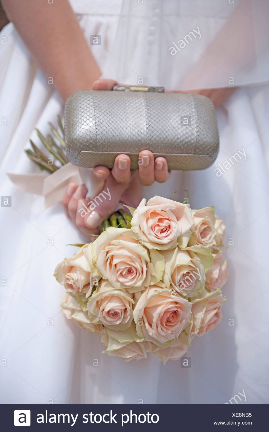 Germany, Bride holding rose bouquet and clutch - Stock Image