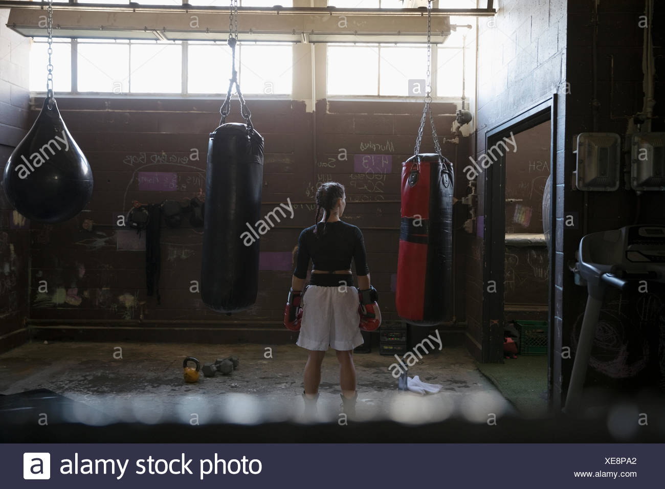 Female boxer standing at punching bags in gritty gym - Stock Image