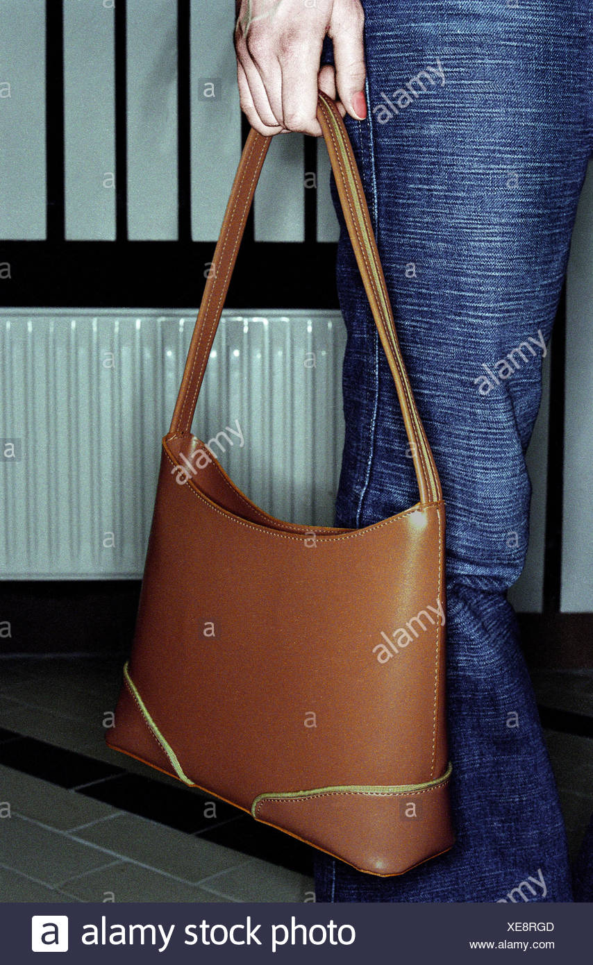 Woman, stand, handbag, detail, trousers, pouch, leather ball pouch, brown, fashion, accessories, hold, wait, inside, very close - Stock Image