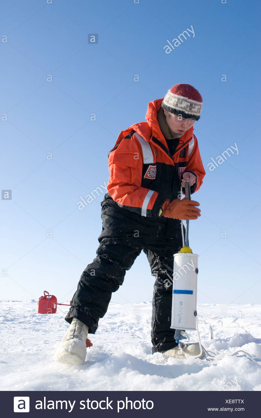 Alaska, Bering Sea. Scientists studying ice condiitons and the changing ecosystem due to global warming. A scientist prepares - Stock Image