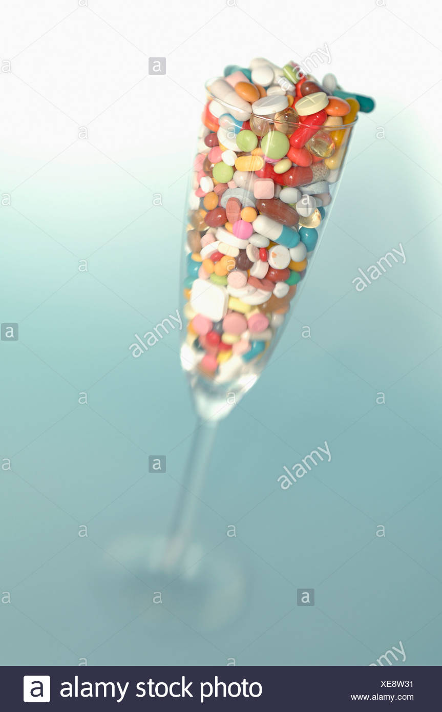 Pills in cocktail glass against coloured background Stock Photo