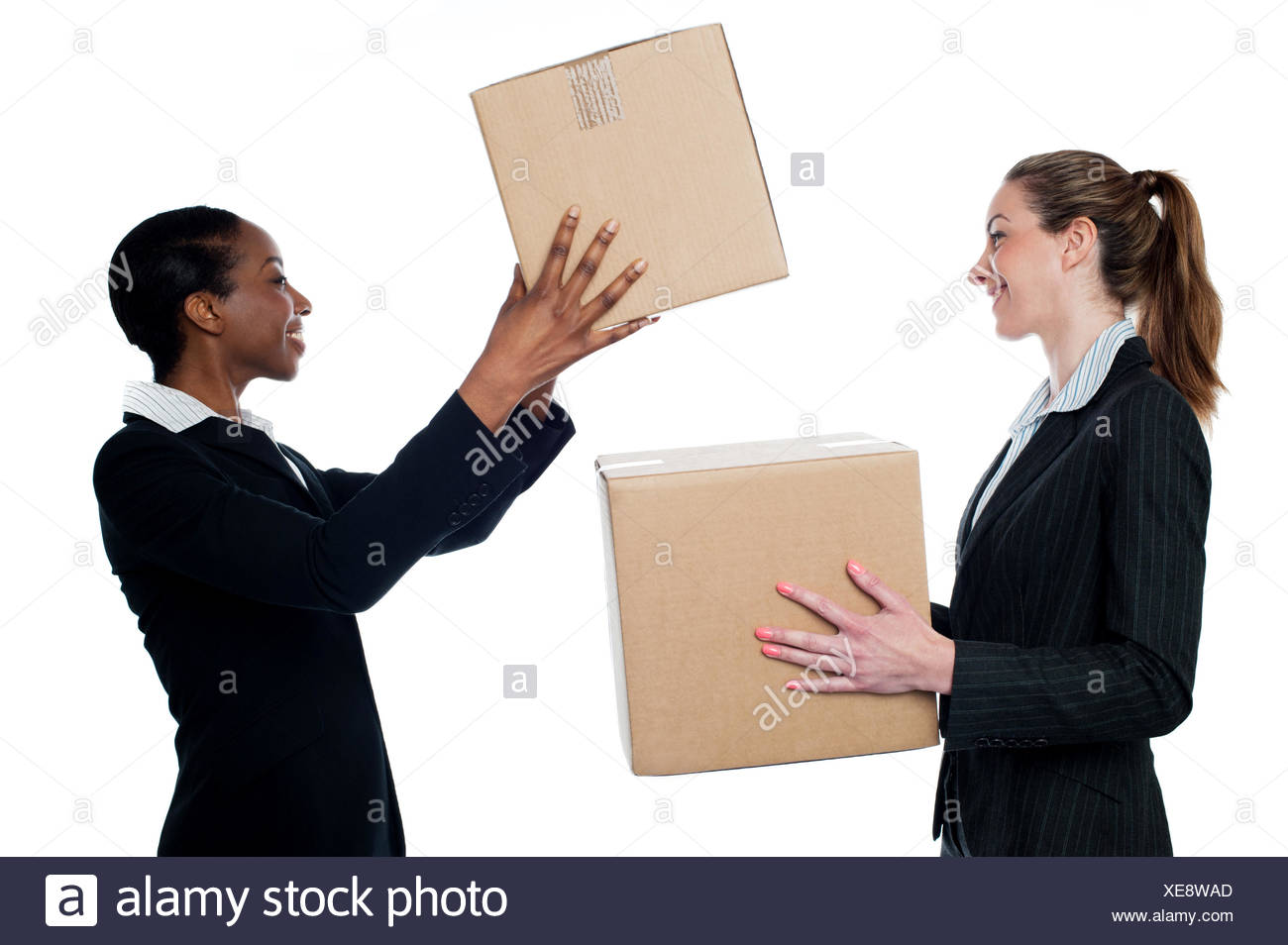 Businesswoman passing packed cartons - Stock Image