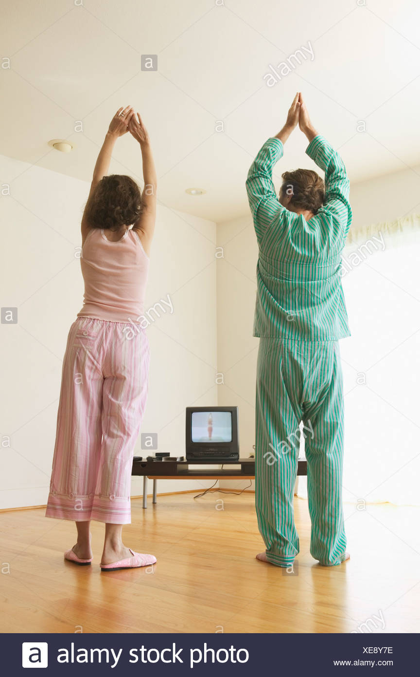 Middle aged couple exercising to a TV program - Stock Image