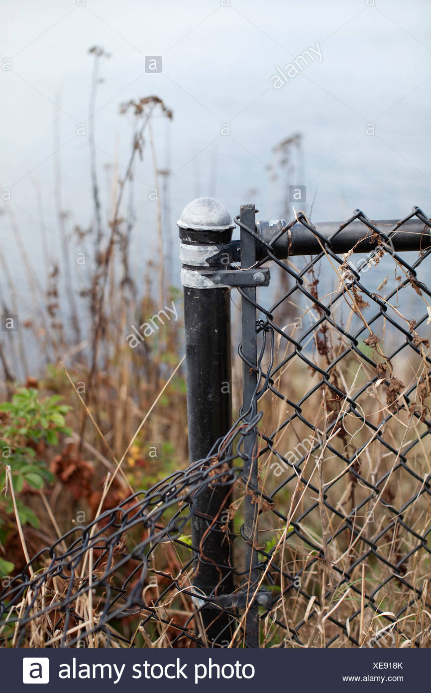 A bent chain-link fence - Stock Image