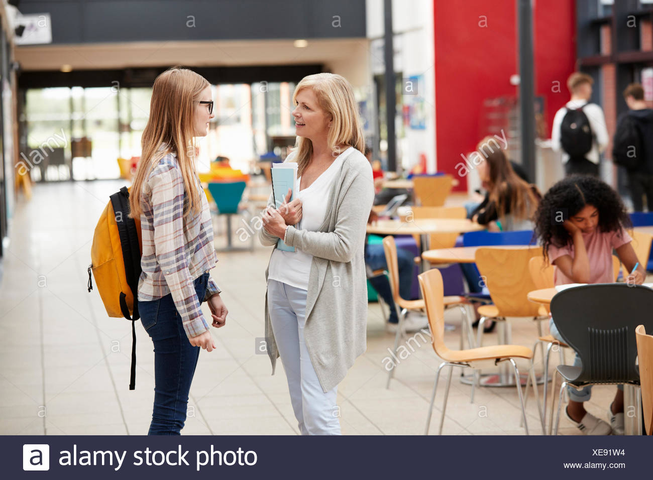 Teacher Talks To Student In Communal Area Of College Campus - Stock Image