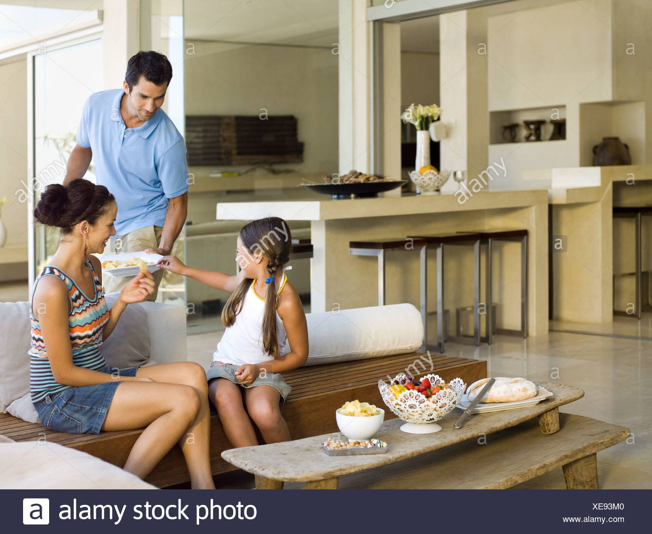 Man serving chips to his wife and daughter - Stock Image