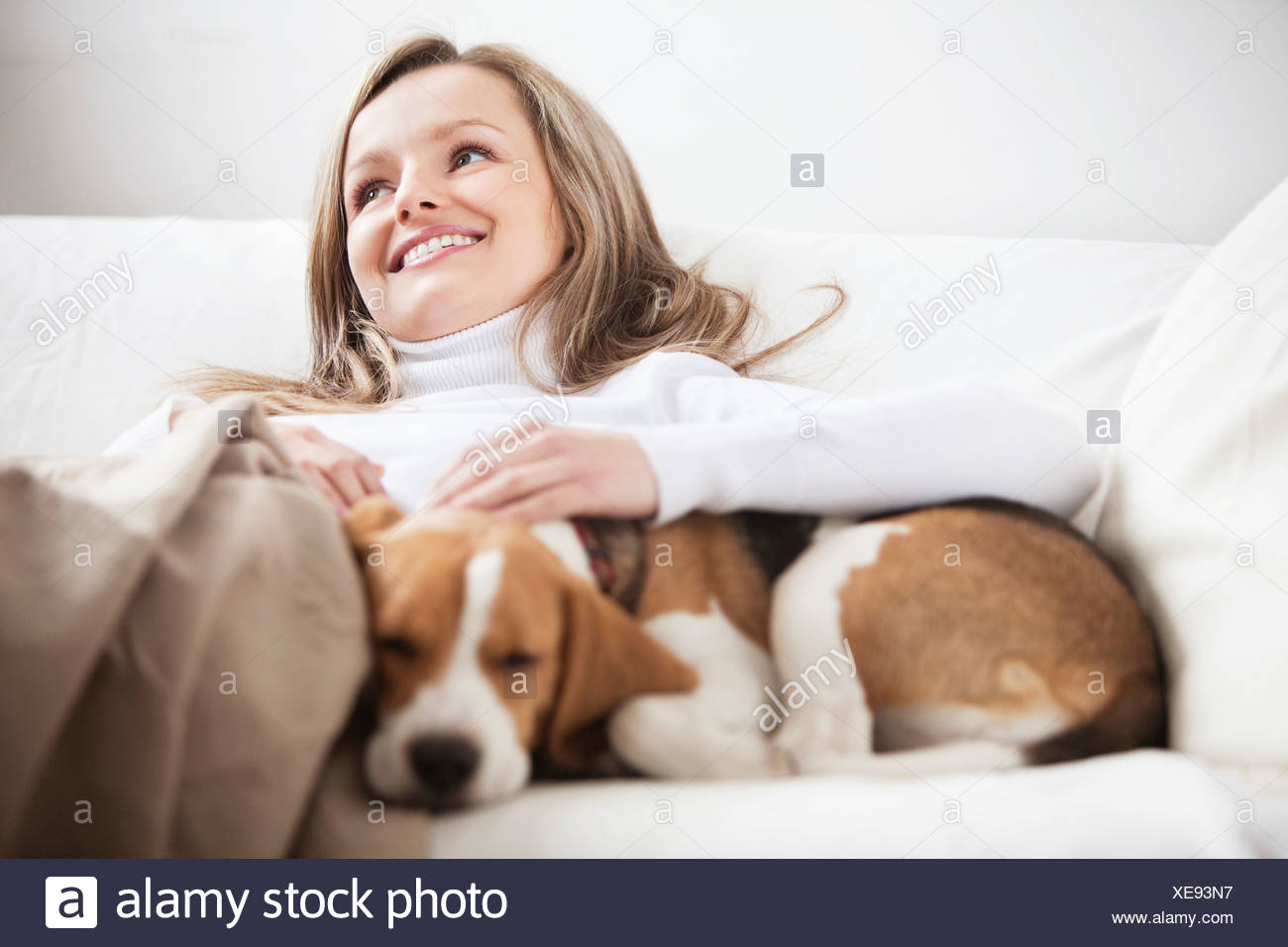 portrait of young woman together on sofa with dog - Stock Image