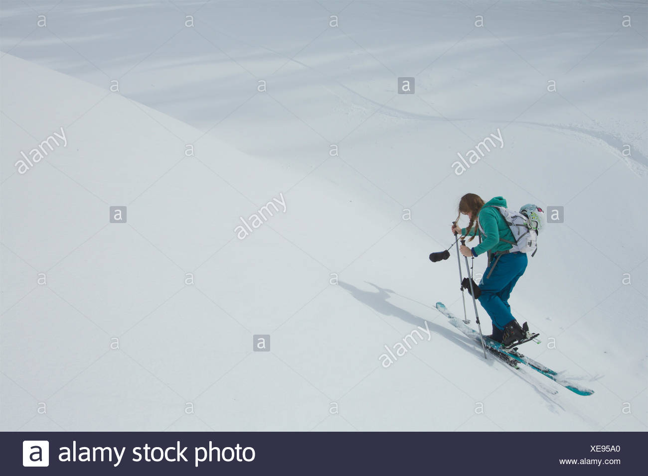 Teen girl skiing uphill with skins on her skis. - Stock Image