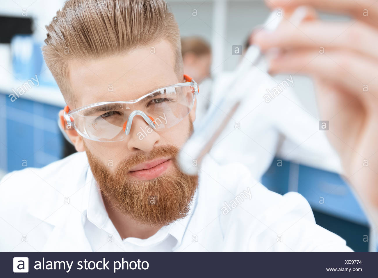 Close-up view of bearded chemist in protective goggles inspecting test tube in lab - Stock Image