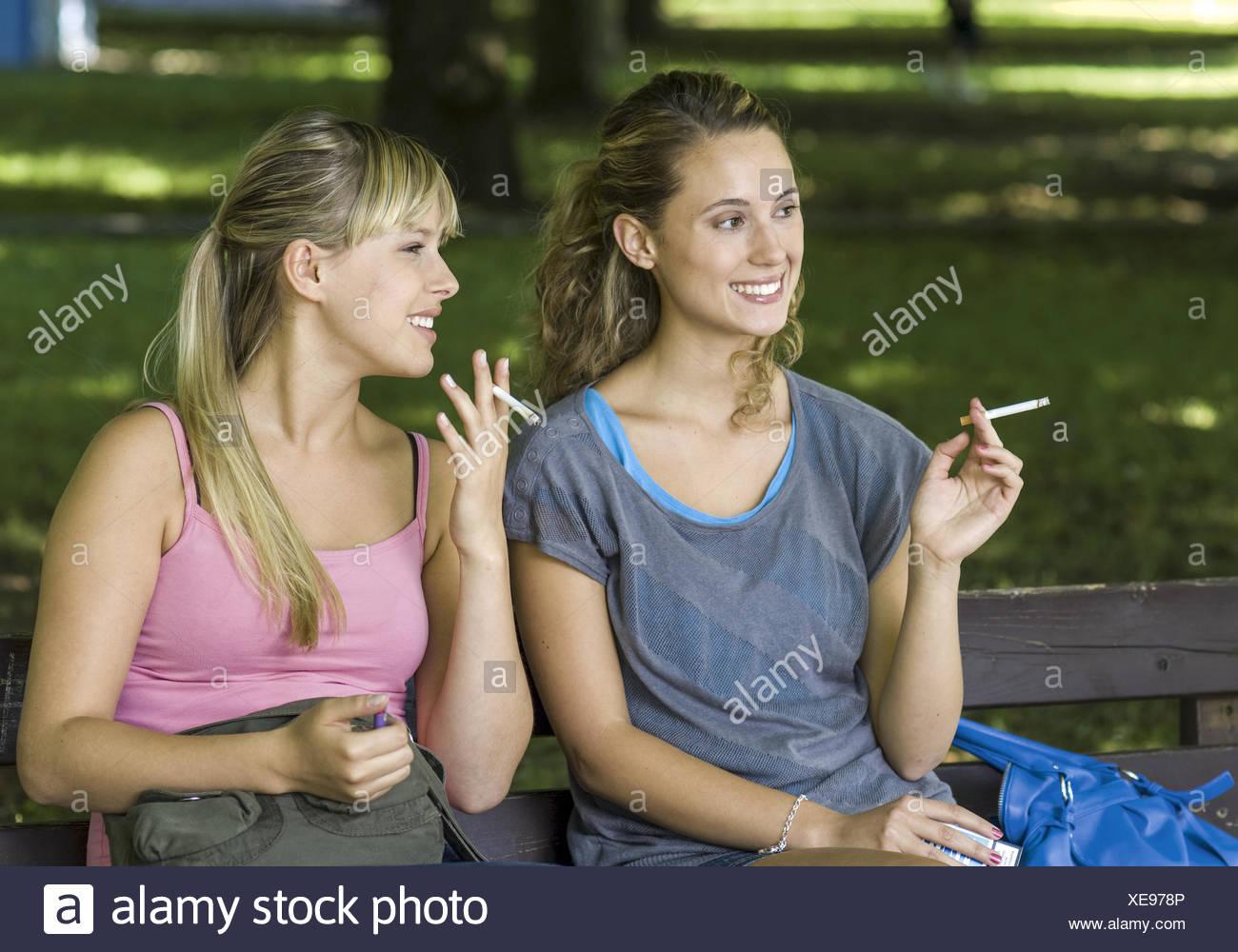 Zwei Teenager-Maedchen rauchen Zigaretten auf Parkbank (model-released) - Stock Image