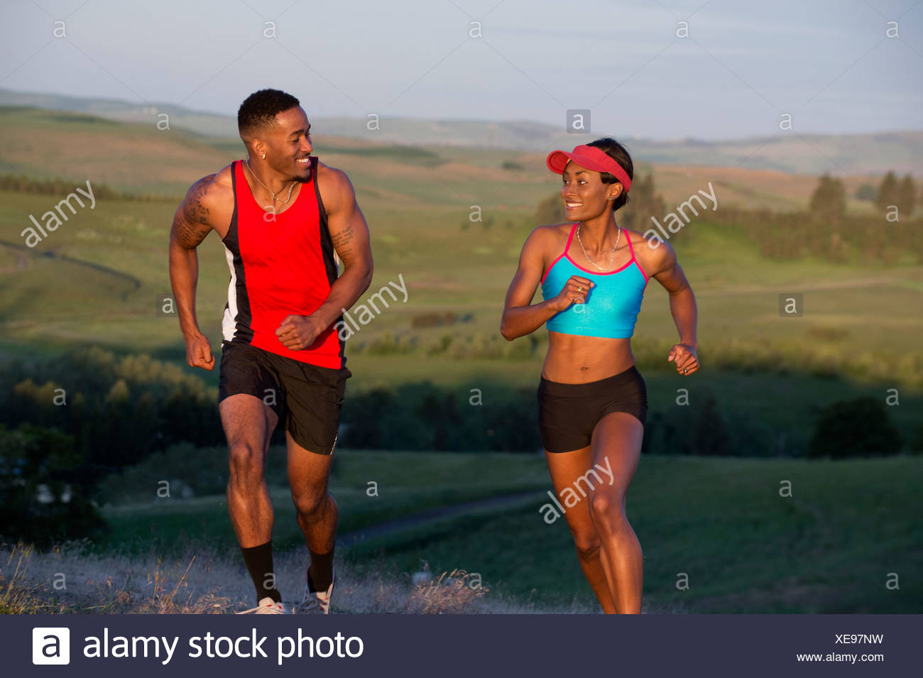 Young couple running in landscape, Othello, Washington, USA Stock Photo