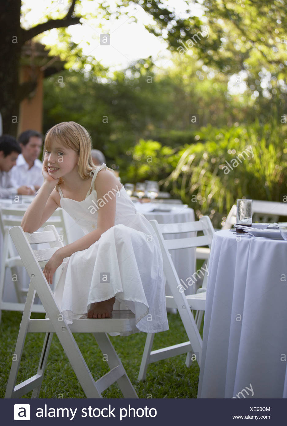 Young girl crouched on chair at outdoor party smiling - Stock Image