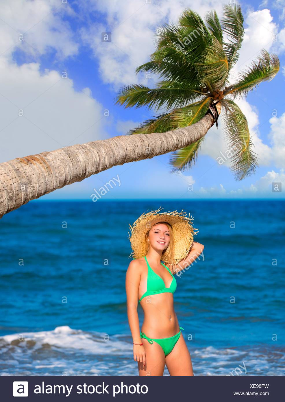 blond tourist girl in a tropical summer beach happy vacations Caribbean coconut palm tree. - Stock Image