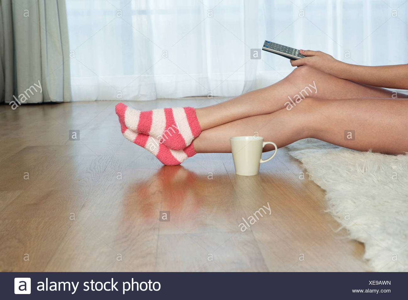 Low angle view of woman in stripey socks holding remote control - Stock Image