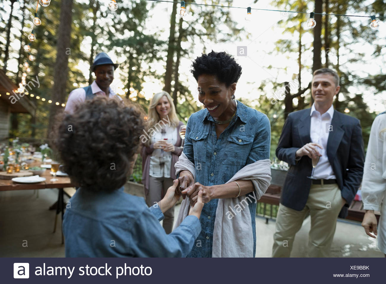 Grandmother and grandson dancing at party on balcony - Stock Image
