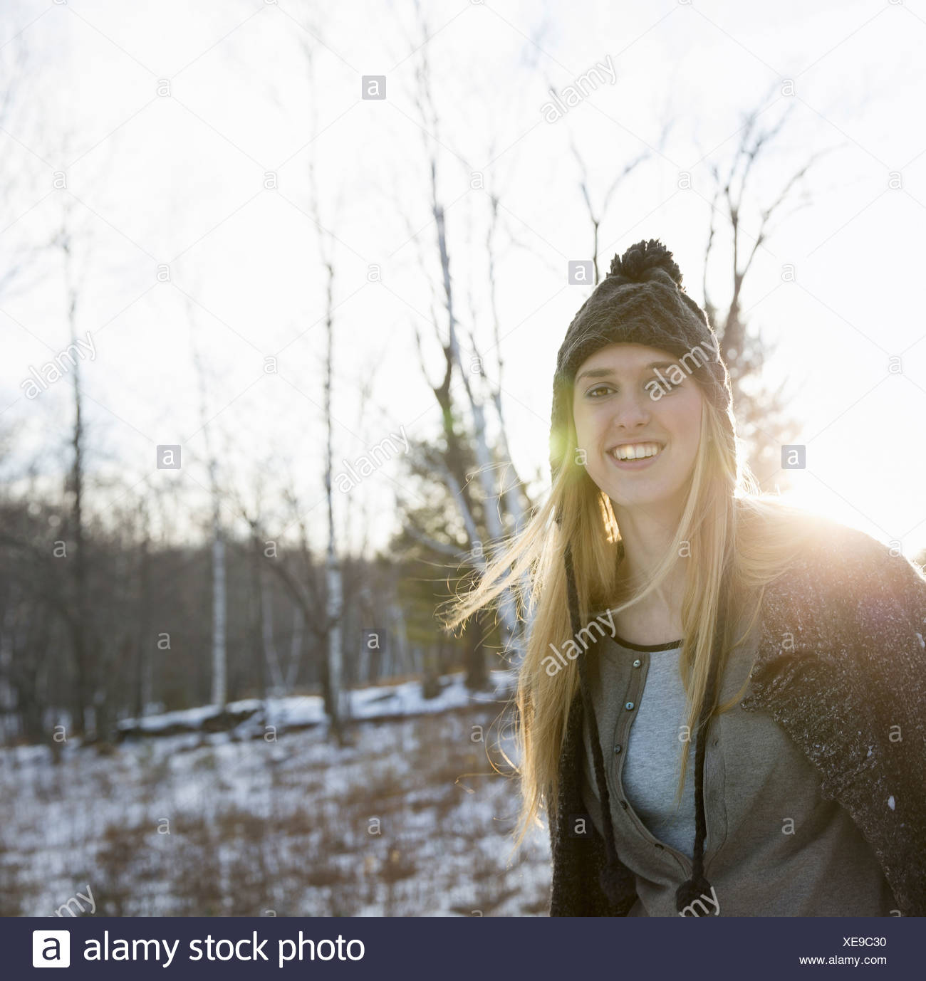 A young woman with blonde hair and a knitted woollen hat and coat Outdoors on a winter's day Snow on the ground - Stock Image