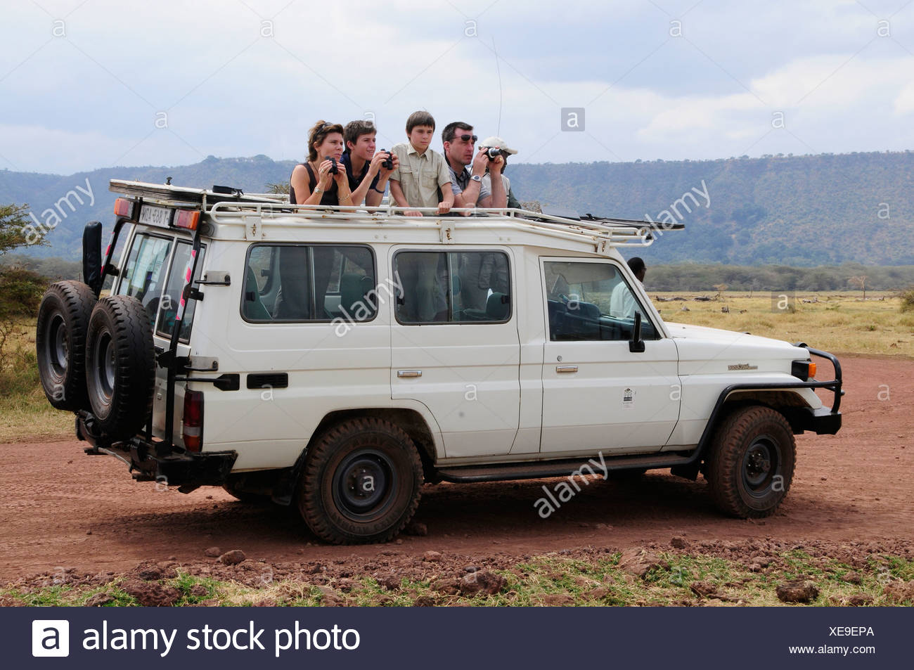 Tourists on safari in a four wheel drive vehicle, Lake Manyara National Park, Tanzania, Africa - Stock Image