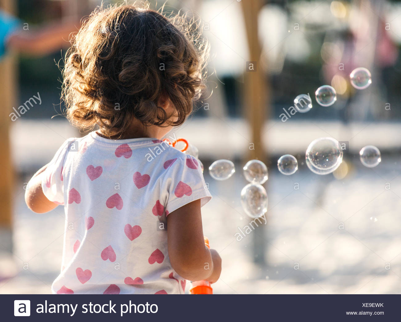 Back view of little girl making soap bubbles at playground - Stock Image
