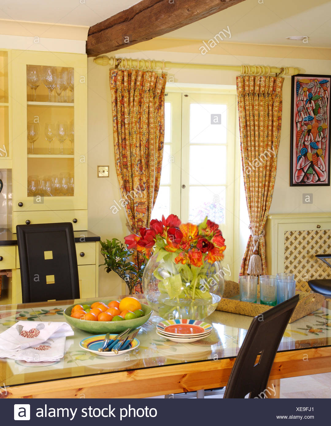 Vase Of Orange Tulips On A Glass Topped Table In Yellow Cottage Dining Room With Patterned