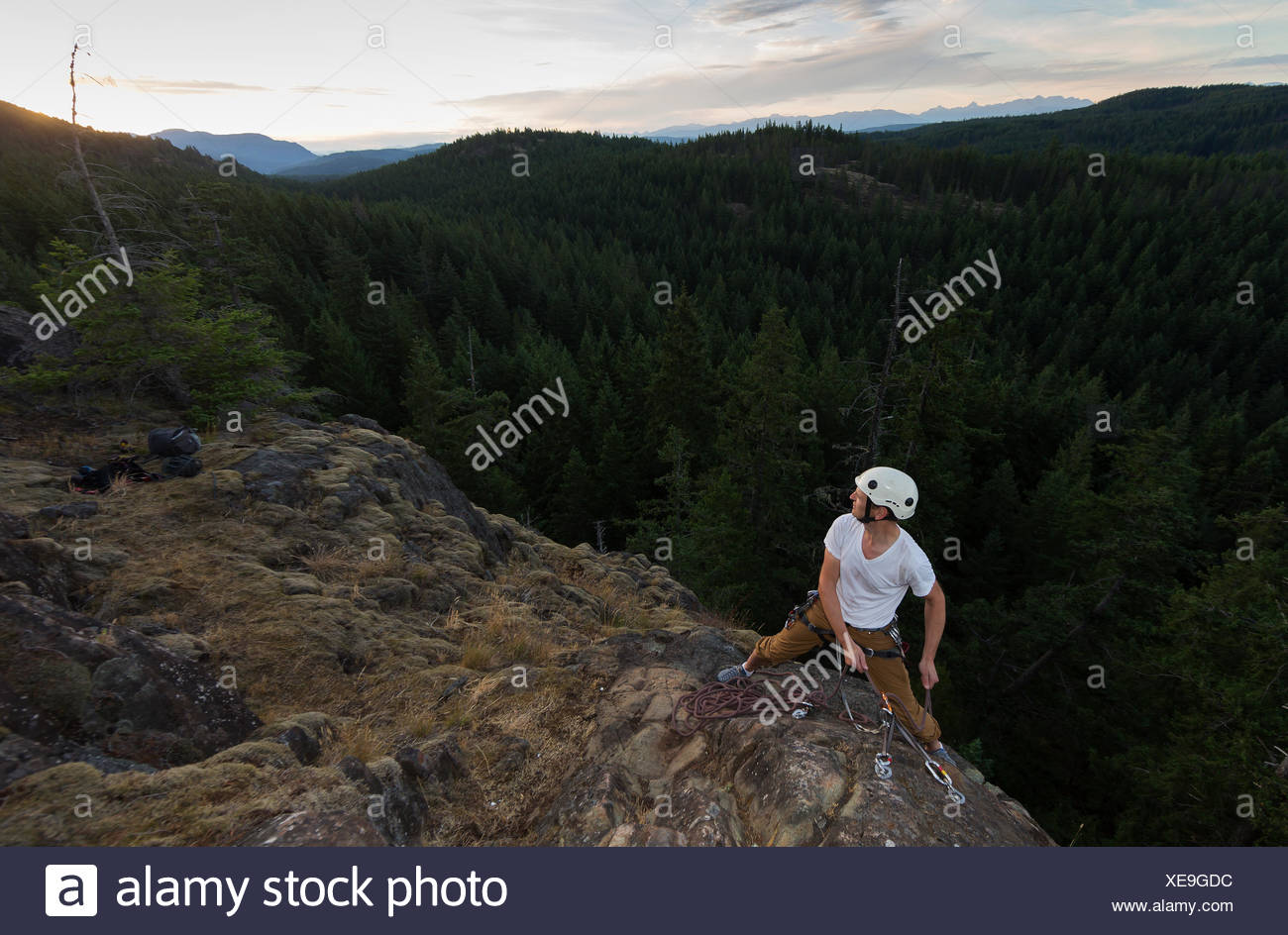 A male climber on Sunset Slab sets up a belay station while climbing on Quadra Island Quadra Island Northern Gulf Islands - Stock Image