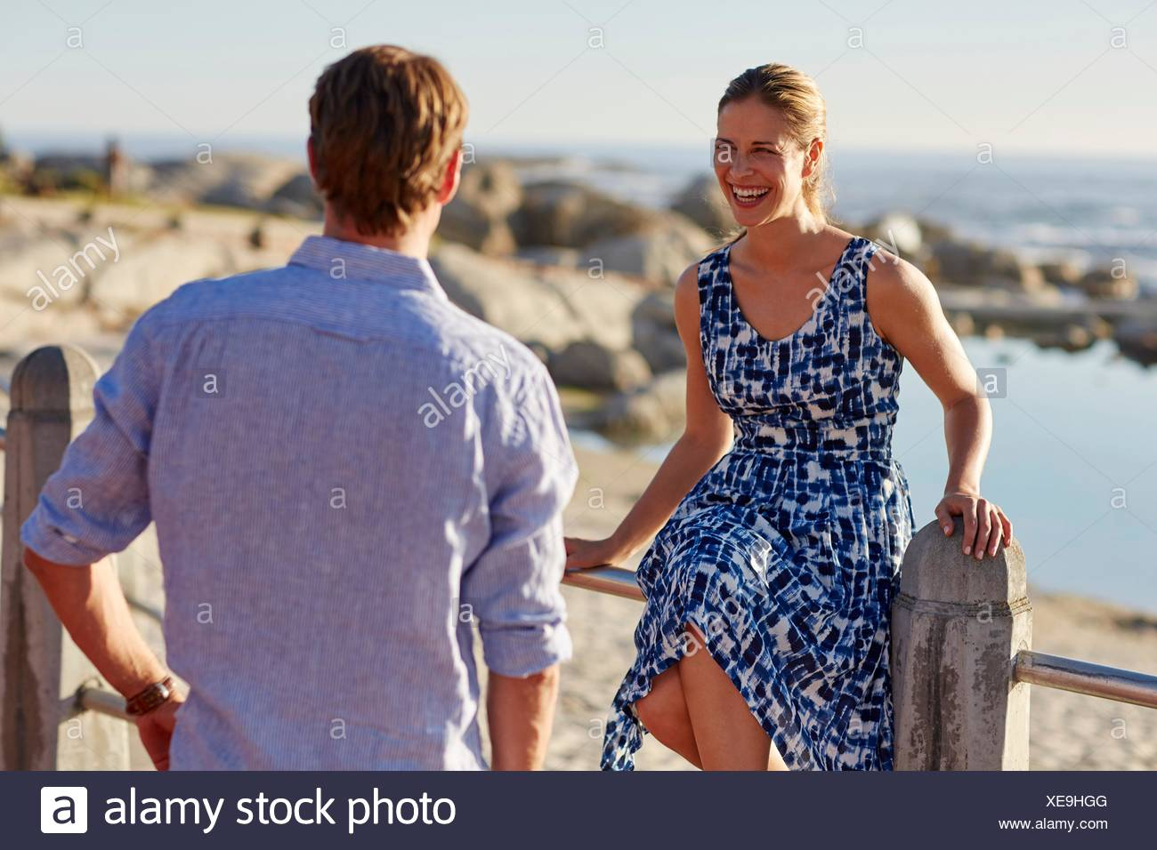 MODEL RELEASED. Woman sitting on railings by beach laughing, man watching. - Stock Image