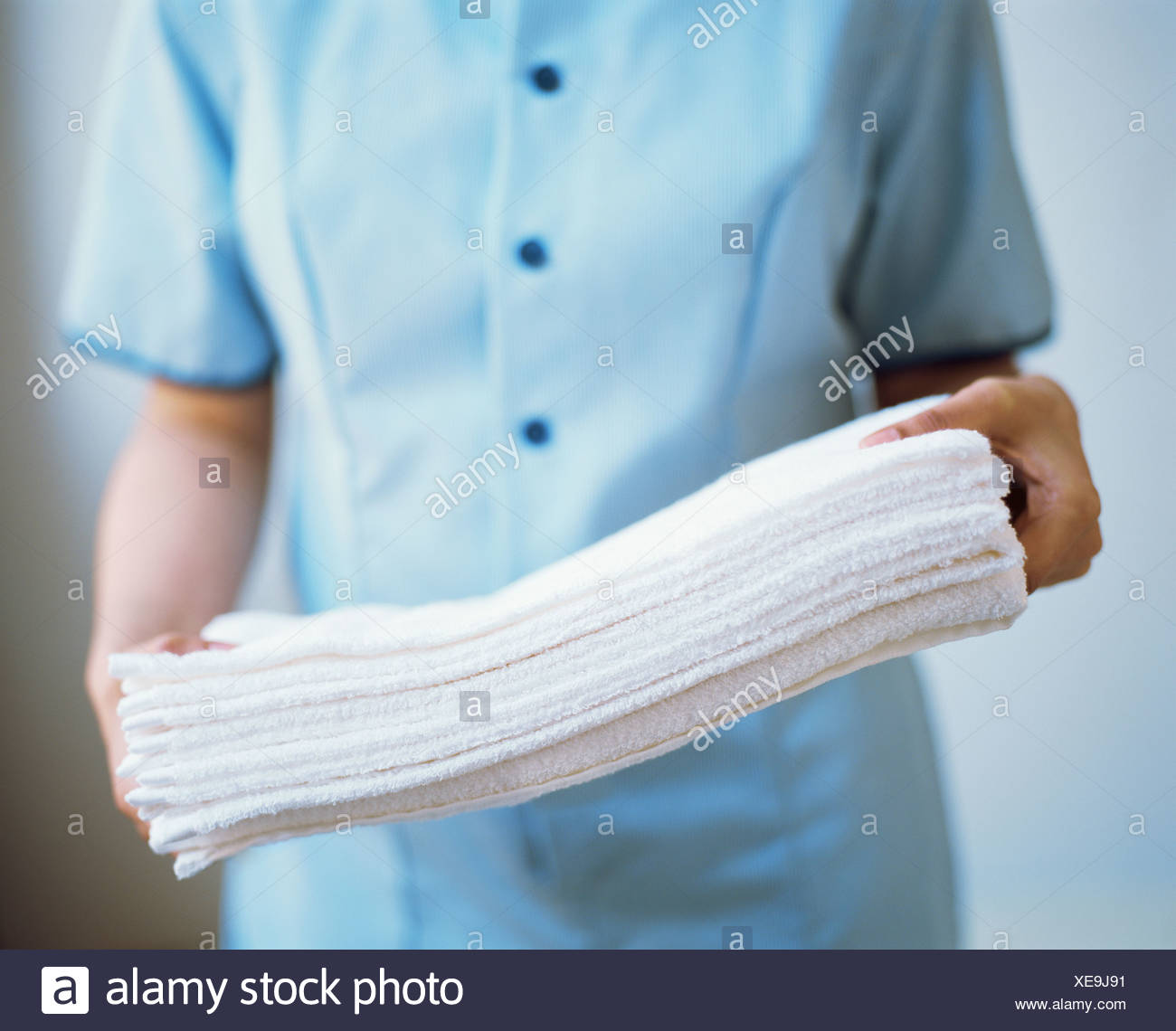Maid carrying towels - Stock Image