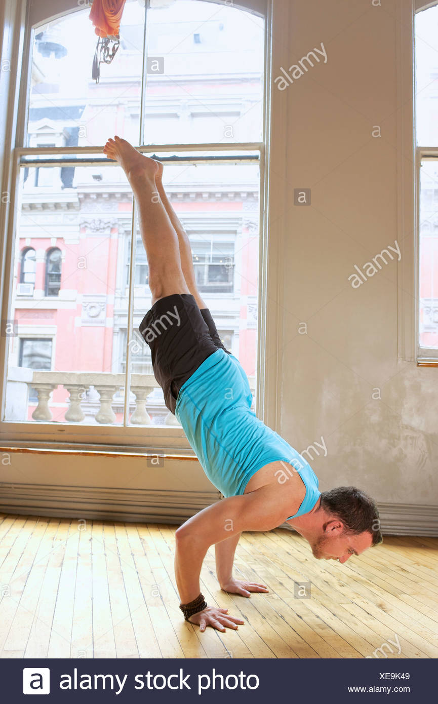 Mid adult man doing handstand - Stock Image
