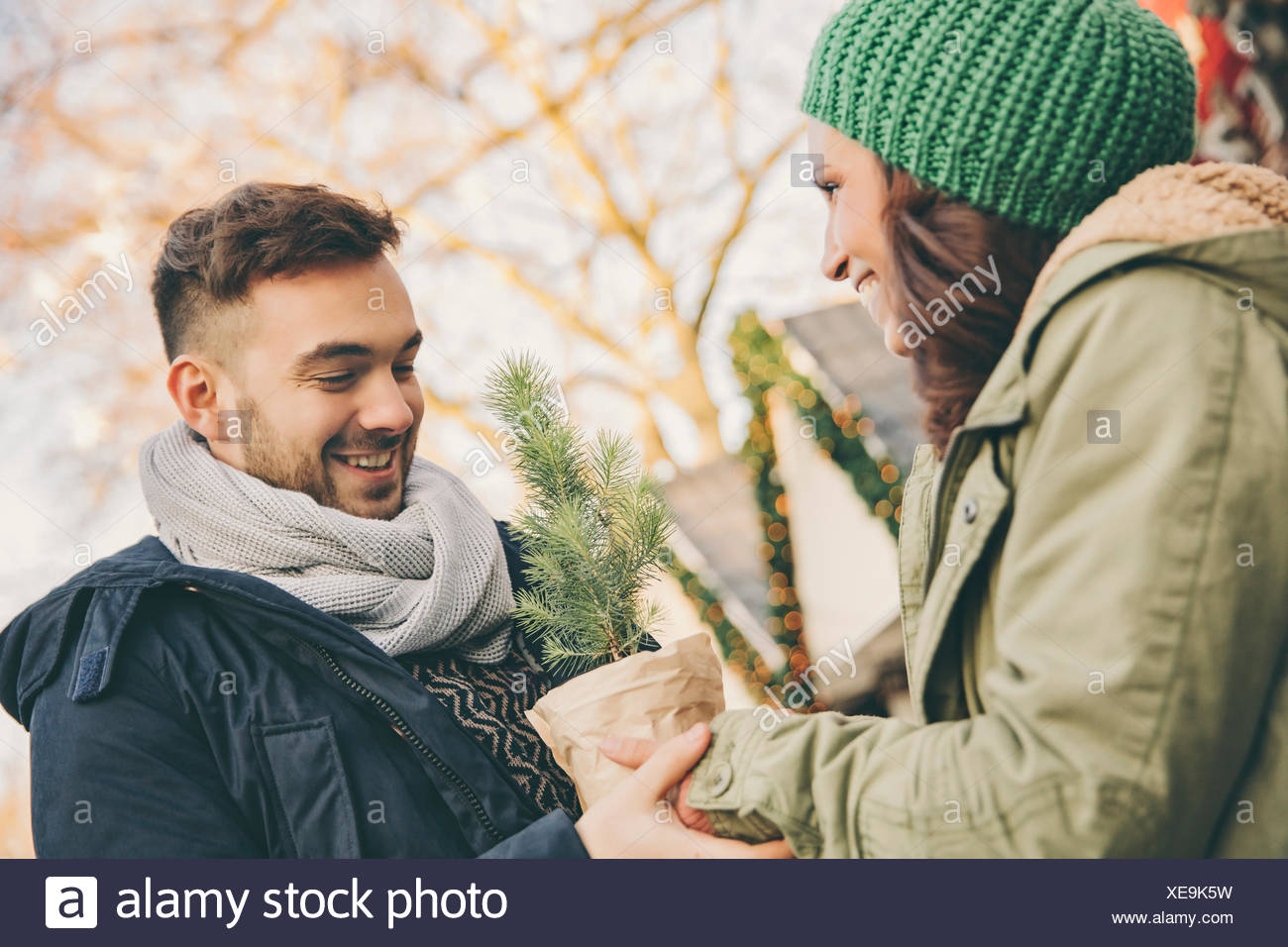 Man receiving a small tree in a pot from a woman on Christmas Market - Stock Image