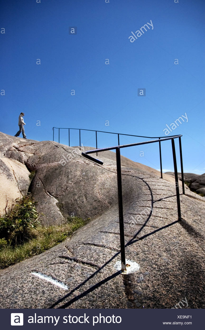 Low angle view of a tourist on a cliff, Vastkusten, Bohuslan, Sweden - Stock Image