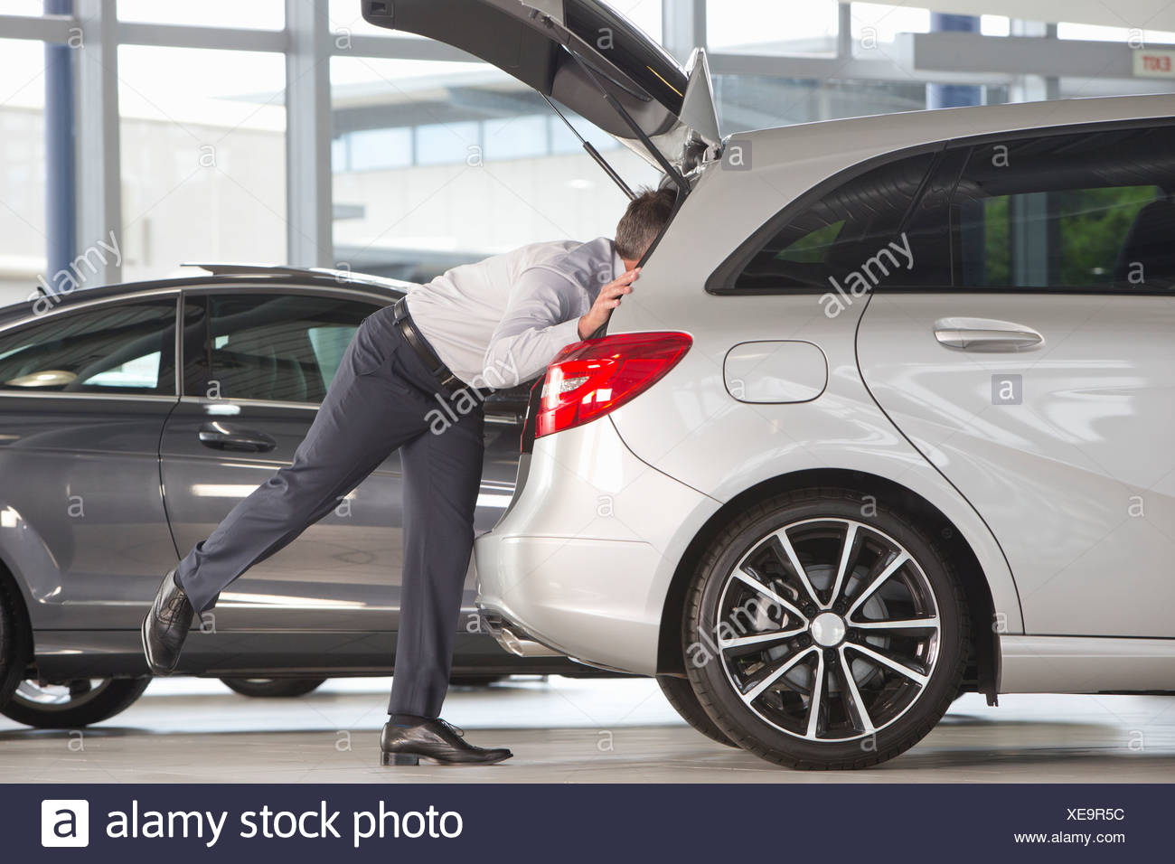 Man looking into hatchback of car in car dealership showroom - Stock Image