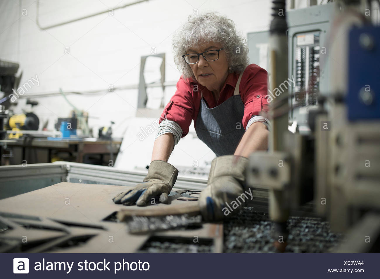 Senior female machinist using machinery in workshop - Stock Image