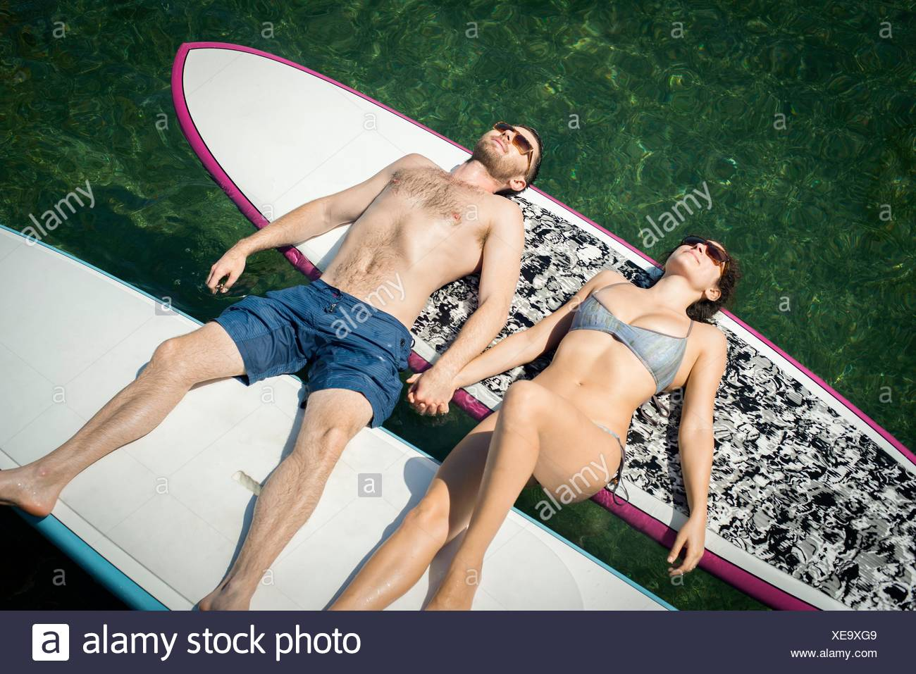 Overhead view of young couple sunbathing on paddleboards - Stock Image