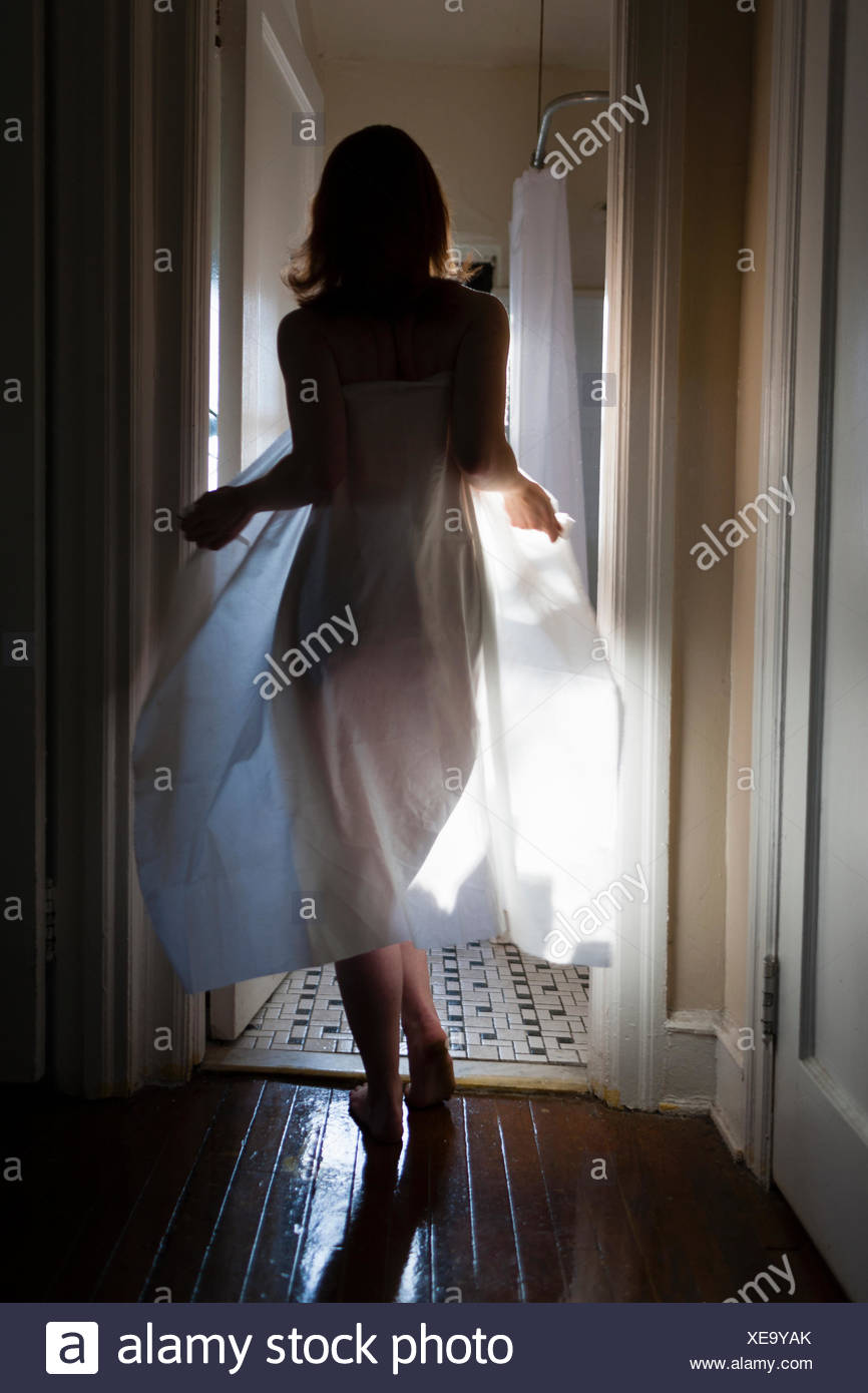 Mid adult woman walking towards bathroom, wrapped in sheet, rear view - Stock Image