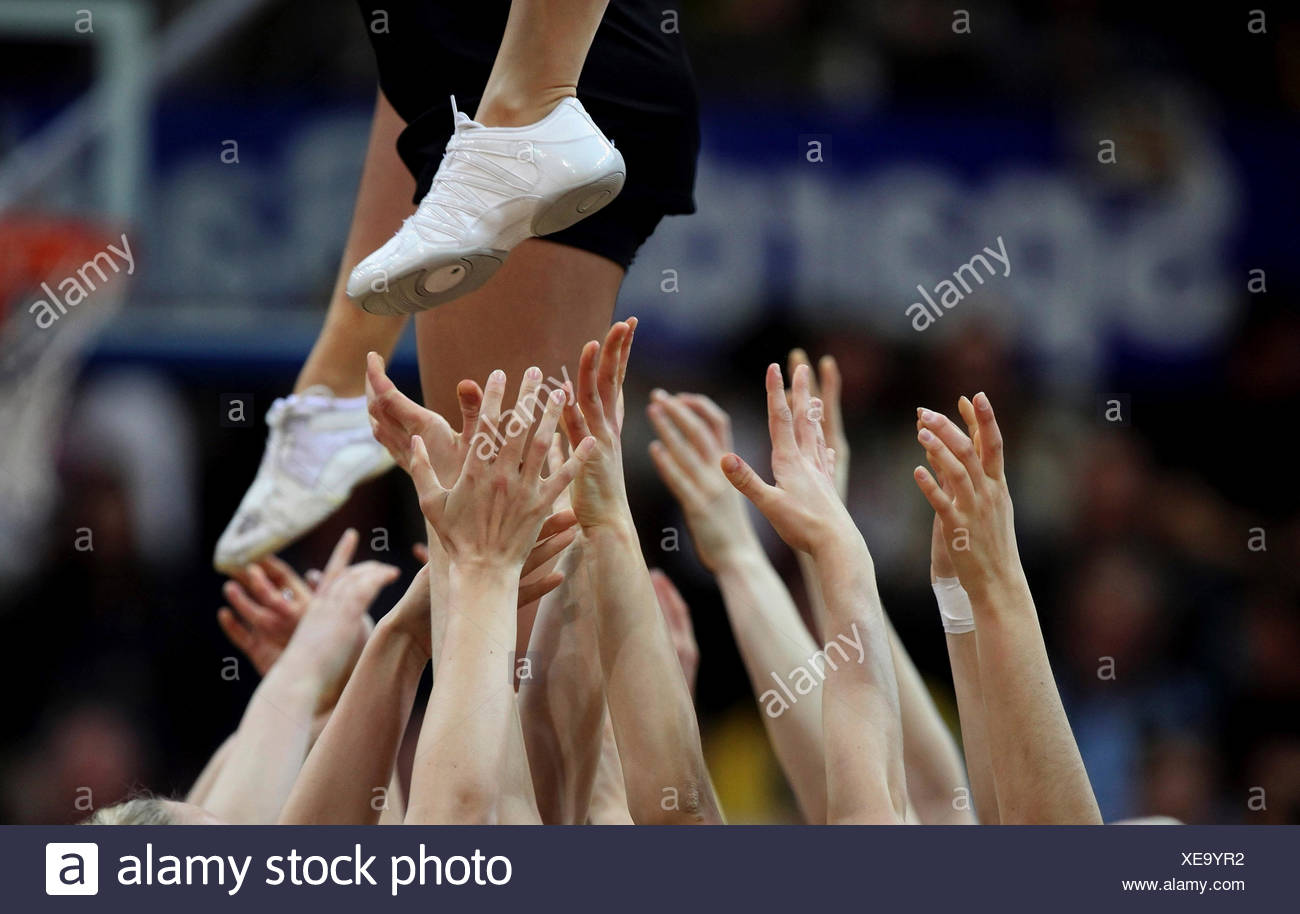 Cheerleaders stretching out their hands to support a cheerleader above - Stock Image