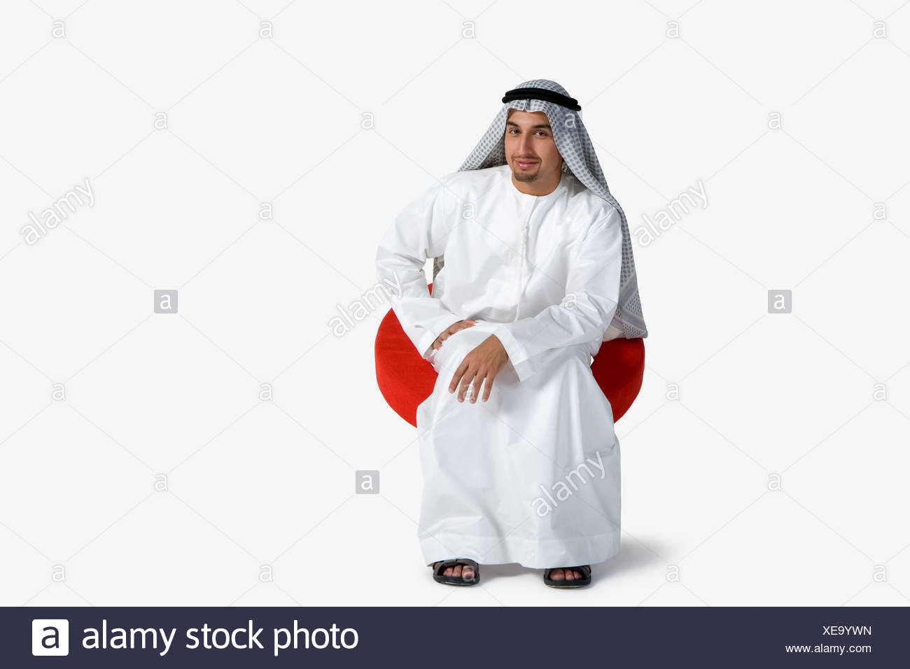 Young man sitting on chair, smiling, portrait Stock Photo