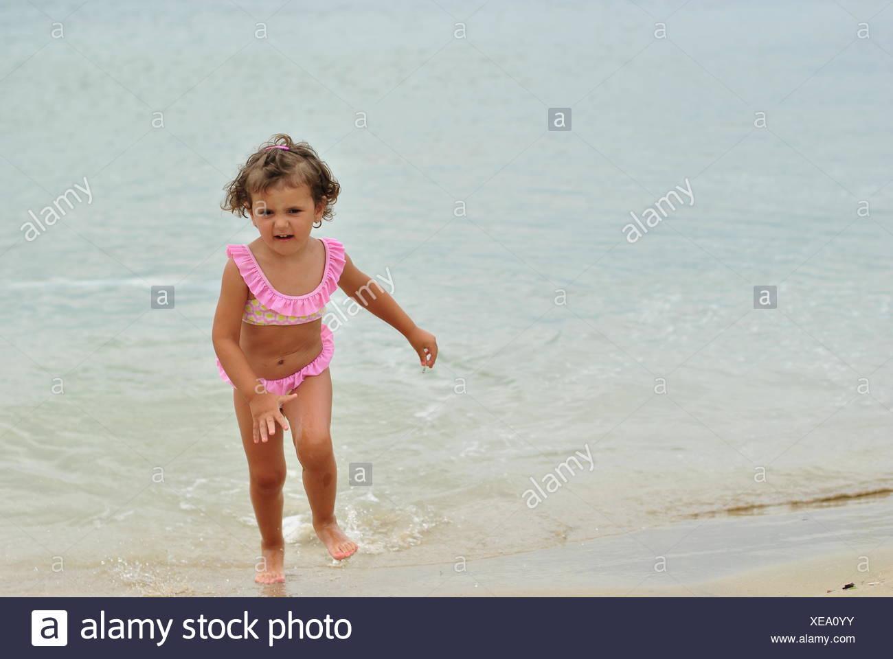 Girl in pink bikini running out of sea - Stock Image