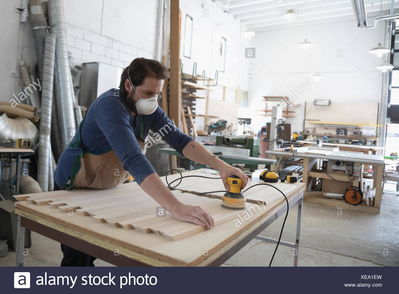Male carpenter wearing protective mask and using sander to sand wood planks in workshop - Stock Image