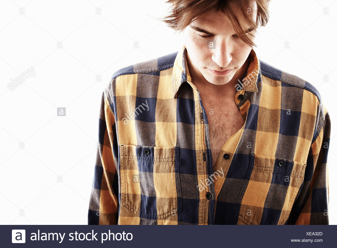 Studio portrait of young man looking down - Stock Image