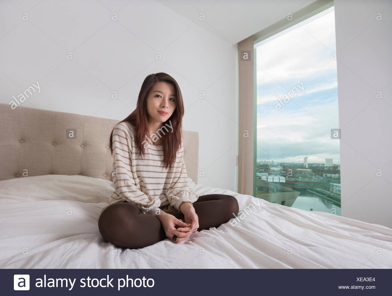 Portrait of beautiful young woman sitting on bed - Stock Image