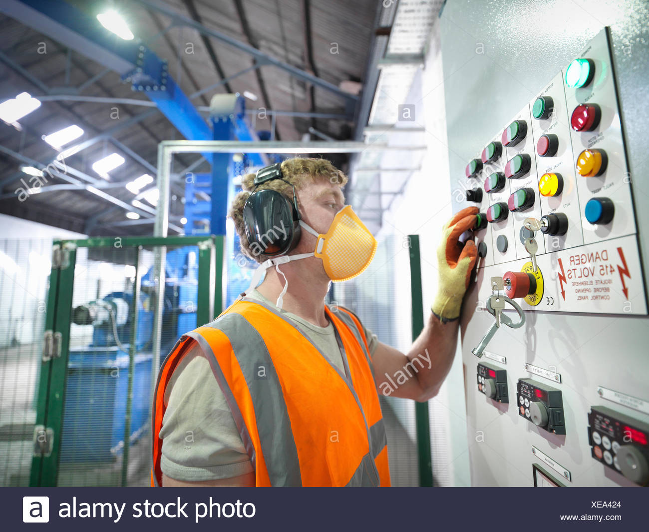 Worker at controls of metal ore grinding mill - Stock Image