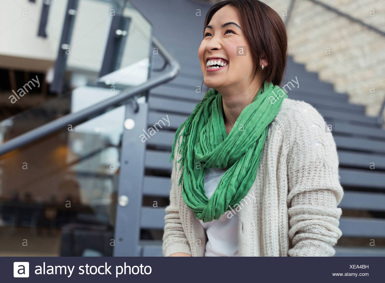 Female student sitting on staircase at college campus - Stock Image