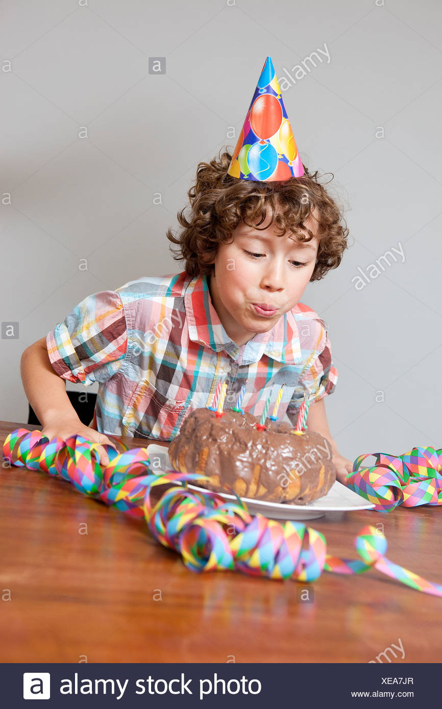 Boy blowing out birthday candle - Stock Image