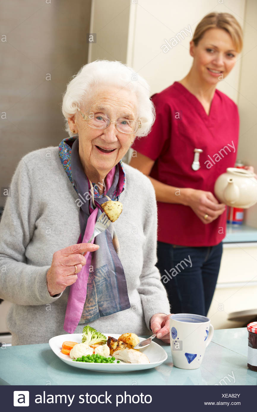 Senior woman with carer eating meal at home - Stock Image