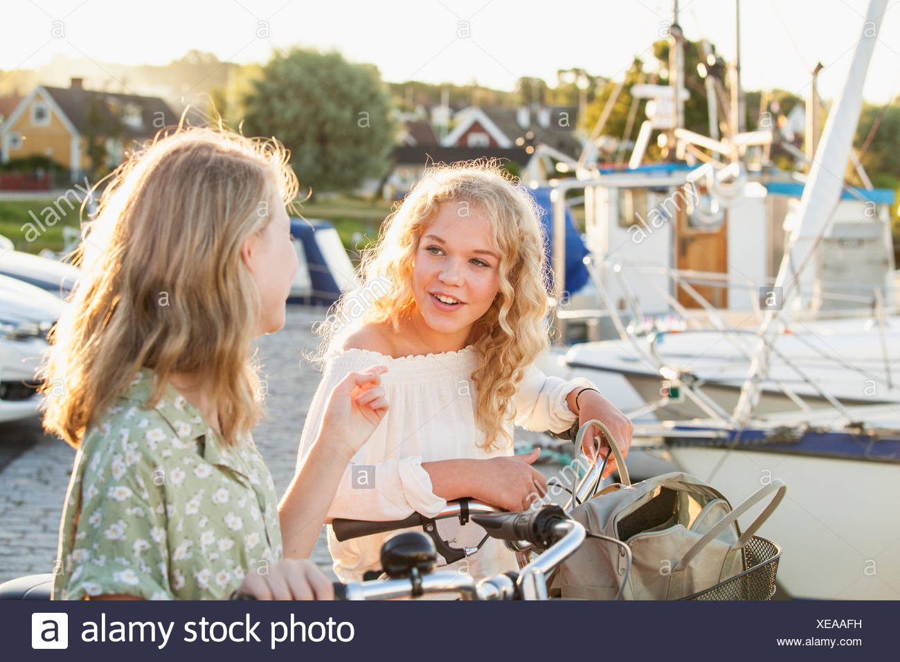 Sweden, Blekinge, Hallevik, Two teenage girls(14-15, 16-17) with bicycles talking at marina bay Stock Photo